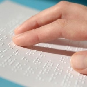 Blind woman reading text in braille
